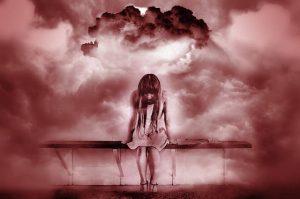 Junge Frau die auf einer Bank übergebeugt sitzt und in eine Tiefe zu schauen scheint. Um sie herum sind defuse Wolken zu sehent