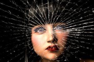 Frauenportrait hinter einer gesplitterten Glasscheibe