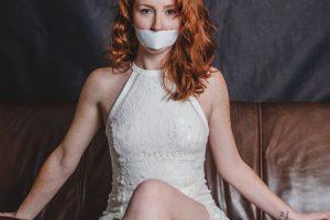 Rothaarige Frau sirtz auf einer Ledercouch und hat den Mund mit weißem Klebeband zugeklebt.