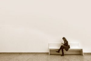 Eine junge Frau die in einem großen leeren Raum auf einer Bank sitzt in in sich versunken auf ein Handy schaut