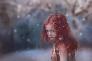 Ein kleines rothaariges Mädchen in einer Schneelandschaft.