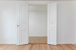 Zwei weiße Räume die mit einer offenen alten Flügeltür verbunden sind. Abgezogene Dielen.