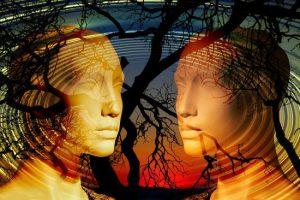 Zwei Puppengesichter mit einer Fotogollage überdeckten transperenzen Spirale und dunklen Baumästen