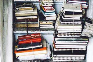Ein altes Regal gefüllt mit in Paketen geschnürten Notizbücher verschiedenster Formen